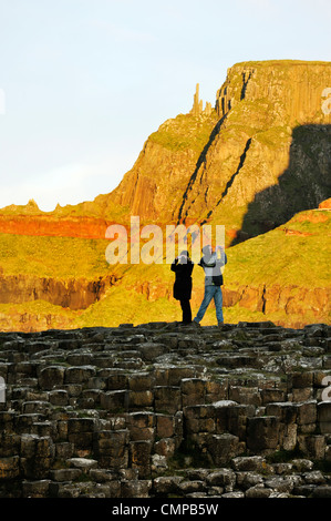 The Giants Causeway, Northern Ireland. Tourist couple take photographs on basalt rock formations known as the Grand - Stock Photo