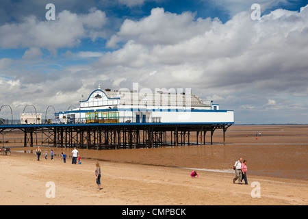 UK, England, Lincolnshire, Cleethorpes, visitors relaxing on beach near pier in summer sunshine - Stock Photo