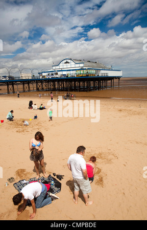UK, England, Lincolnshire, Cleethorpes, families relaxing on beach near pier in summer sunshine - Stock Photo