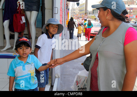 Peru Tacna Calle San Martinsidewalk storefront Hispanic woman boy mother son child parent holding hand fearful holding - Stock Photo