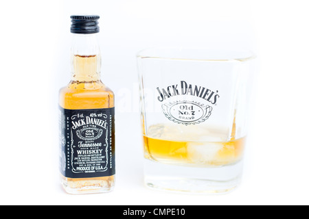A miniature Jack Daniels bottle and glass of whiskey. Jack Daniels Old No. 7 is a brand of sour mash Tennessee whiskey. - Stock Photo