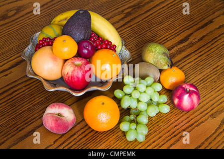 Selection of colorful, fresh, natural looking fruit in an old bowl on wooden background - Stock Photo