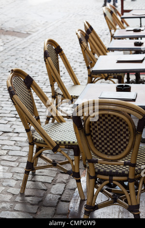 Row of empty restaurant tables and chairs of a street cafe in Belgium Europe close up - Stock Photo