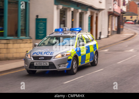 A Police car on a shout with blue lights flashing in Norwich , Norfolk , England , Britain , Uk - Stock Photo