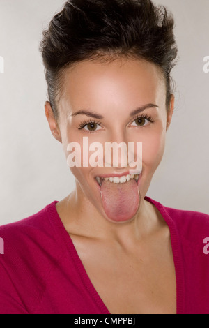 Woman poking tongue out - Stock Photo