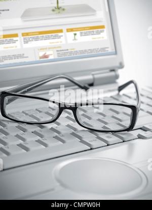 Pair of glasses sitting on laptop keyboard - Stock Photo