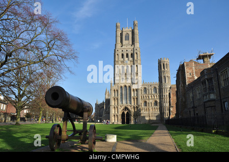 The west tower of Ely Cathedral from Palace Green with the cannon which was captured from the Russians in Sebastopol - Stock Photo
