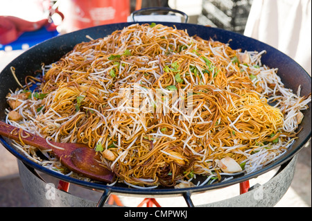 noodles being cooked in a large wok - Stock Photo