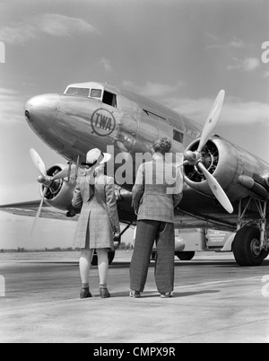 1940s REAR VIEW OF BOY & GIRL STANDING TOGETHER LOOKING AT PROPELLER AIRPLANE OUTDOOR - Stock Photo