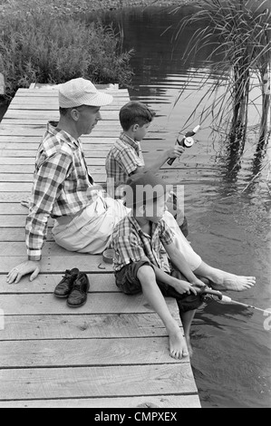 1950s 1960s FATHER WITH TWO SONS SITTING ON DOCK FISHING TOGETHER OUTDOOR BY POND - Stock Photo