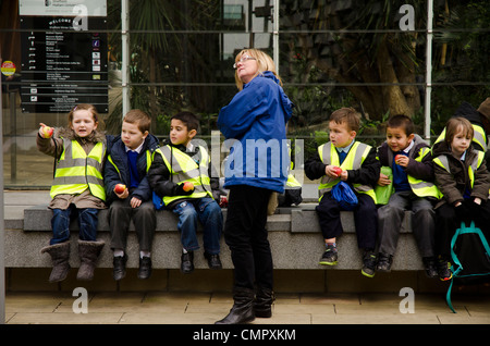 Class of young schoolchildren on excursion in Sheffield, UK. Note they're all eating apples, not junk food. - Stock Photo