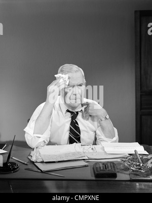 1950s BUSINESSMAN SITTING AT DESK WIPING FOREHEAD WITH HANDKERCHIEF PULLING AT SHIRT COLLAR - Stock Photo