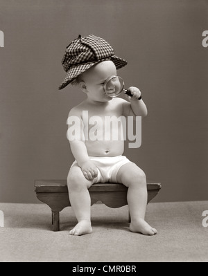 1940s BABY SHERLOCK HOLMES IN DIAPER SITTING ON BENCH WEARING DEER STALKER HAT LOOKING THROUGH MAGNIFYING GLASS - Stock Photo