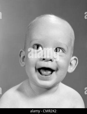 1960s CLOSE-UP PORTRAIT OF NEARLY BALD BABY SMILING WITH MOUTH WIDE OPEN LOOKING OFF TO THE SIDE - Stock Photo