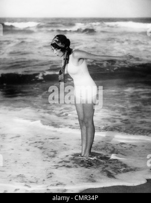1920s WOMAN WEARING BATHING SUIT & HEAD SCARF LOOKING DOWN AT WATER STANDING IN OCEAN SURF - Stock Photo