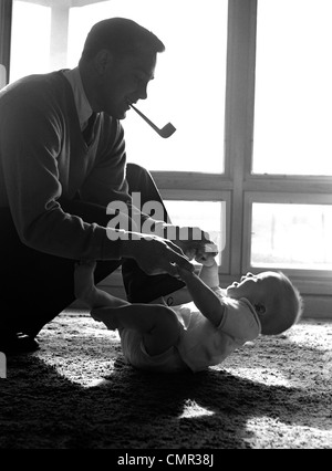 1950s FATHER PIPE IN MOUTH KNEELING DOWN TO PLAY WITH BABY LAYING ON FLOOR SUNLIGHT COMING IN THROUGH WINDOWS - Stock Photo