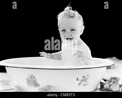 1930s 1940s SMILING HAPPY BABY SITTING IN ENAMELED TIN BATHTUB - Stock Photo
