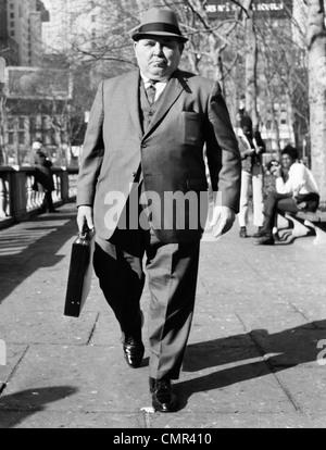 1960s OVERWEIGHT BUSINESSMAN WITH BRIEFCASE SMOKING CIGAR WALKING ON CITY SIDEWALK - Stock Photo