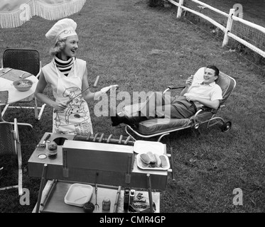 1950s 1960s WOMAN IN CHEF'S HAT AND APRON GRILLING HOT DOGS ON GRILL MAN IN CHAISE LONGUE LAUGHING EATING A FRANKFURTER - Stock Photo