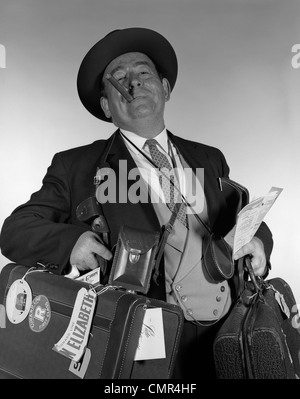 1950s 1960s HEAD-ON PORTRAIT OF CIGAR SMOKING TOURIST CARRYING LOTS OF LUGGAGE LOOKING AT CAMERA - Stock Photo