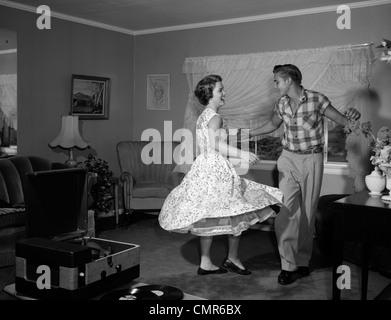 1950s 1960s TEEN COUPLE DANCING JITTERBUG IN LIVING ROOM - Stock Photo