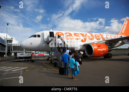 passengers boarding easyjet aircraft at belfast international airport northern ireland uk. - Stock Photo