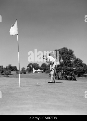 1950s MAN PLAYING GOLF PUTTING GOLF BALL ON GREEN TO FLAG AND CUP OUTDOOR - Stock Photo