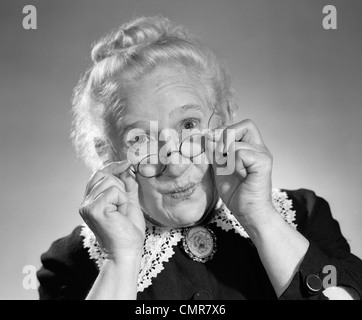 1950s PORTRAIT OF SMILING OLD LADY HOLDING HER ANTIQUE WIRE FRAME GLASSES - Stock Photo
