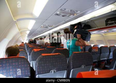 passengers placing bags in overhead lockers of easyjet aircraft at belfast international airport northern ireland - Stock Photo