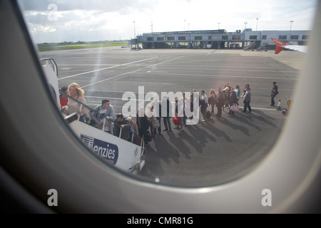 looking out at long queue of passengers boarding easyjet aircraft at belfast international airport northern ireland - Stock Photo