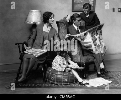 1920s FAMILY OF FOUR MOTHER FATHER SON DAUGHTER IN LIVING ROOM READING NEWSPAPER TOGETHER INDOOR - Stock Photo