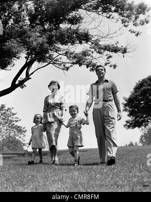 1950s HAPPY FAMILY MOTHER FATHER DAUGHTER SON WALKING IN PARK - Stock Photo