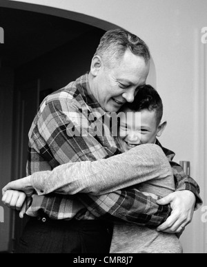 1950s 1960s SMILING FATHER AND SON HUGGING INDOOR - Stock Photo
