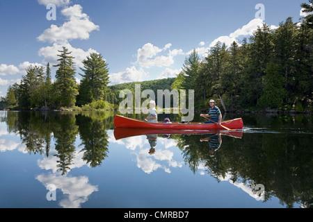 Senior couple canoeing on Smoke Lake, Algonquin Park, Ontario - Stock Photo