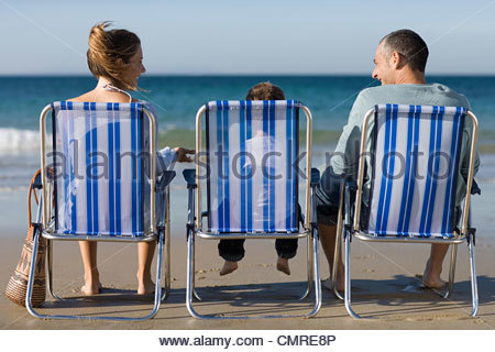Family in deckchairs by the sea - Stock Photo