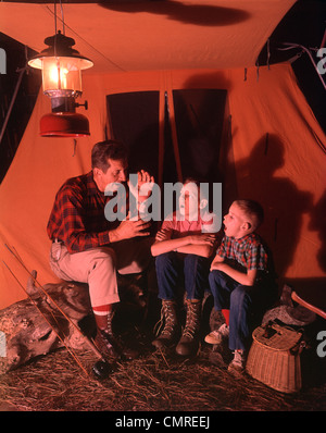 1960s 1970s  GRANDFATHER TELLING SCARY STORY TO BOYS BY TENT AT NIGHT CAMPSITE IN SHADOWS - Stock Photo