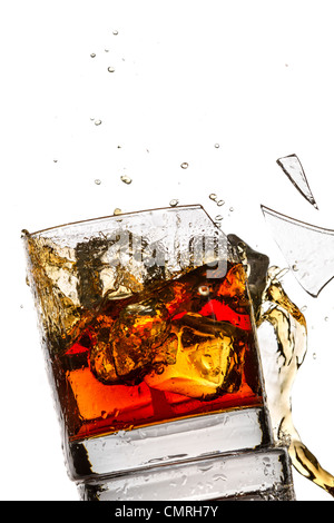 Ice cubes breaking whiskey glass filled with bourbon on white background - Stock Photo