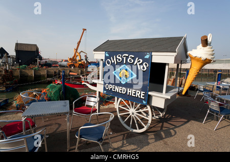The seaside town of Whitstable showing the working harbour and seating outside. - Stock Photo