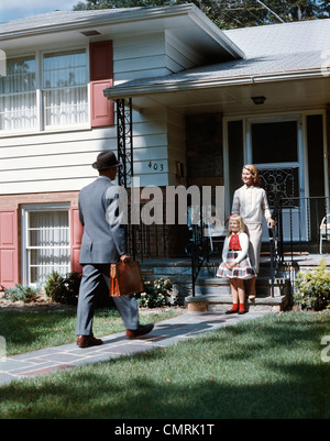 1950s MOTHER DAUGHTER WAITING STEPS HOUSE FOR FATHER BRIEFCASE COMING HOME SUBURBAN FAMILY MAN WOMAN GIRL RETRO - Stock Photo