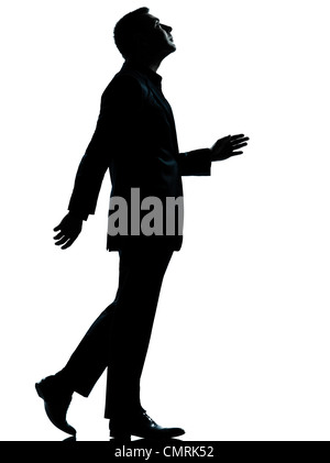 one caucasian business man walking looking up silhouette Full length in studio isolated on white background - Stock Photo