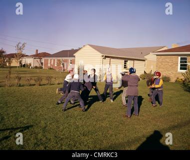 1950s 1960s GROUP NEIGHBORHOOD BOYS PLAY TOUCH FOOTBALL BACKYARD SUBURBAN HOUSES - Stock Photo
