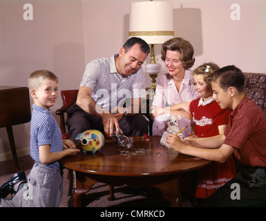 1960s COUNTING MONEY FROM PIGGY BANKS GLASS JAR SAVINGS FINANCE MAN WOMAN BOYS GIRL MOTHER FATHER KIDS RETRO - Stock Photo