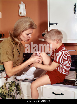 MOTHER GIVING FIRST-AID PUTTING BAND-AID ON KNEE OF SON IN KITCHEN 1960s - Stock Photo