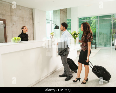 Business people arriving at hotel reception area - Stock Photo