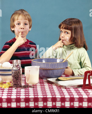 1970 1970s RETRO BOY GIRL BROTHER SISTER MAKING COOKIES TASTING BATTER CHOCOLATE CHIPS BAKING COOKING - Stock Photo