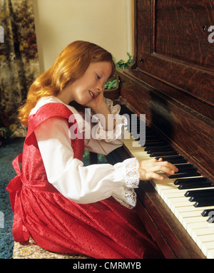 1980s SMILING YOUNG GIRL REDHEAD SITTING AT OLD UPRIGHT PIANO DAYDREAMING - Stock Photo