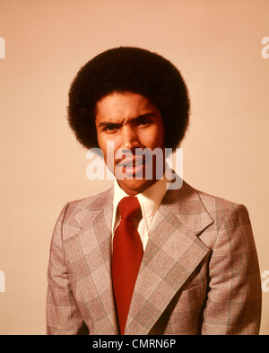 1970 1970s AFRICAN-AMERICAN YOUNG MAN SERIOUS WORRIED WORRY ANXIOUS ANGRY FACIAL EXPRESSION AFRO HAIRDO HAIR DO - Stock Photo