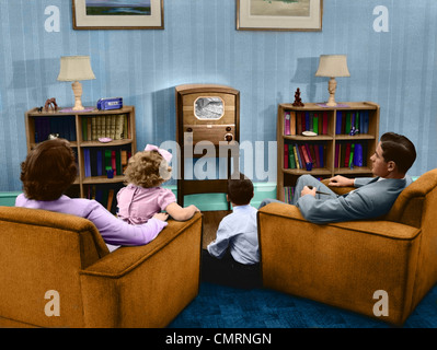 1940s 1950s FAMILY WATCHING TELEVISION IN LIVING ROOM - Stock Photo