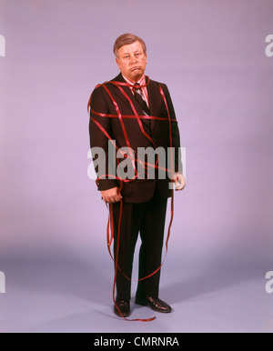 1970 1970s MIDDLE AGED MAN BUSINESS SUIT DISAPPOINTED DEPRESSED UNHAPPY RED TAPE RIBBON TIED UP - Stock Photo