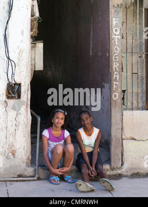 Two young Cuban kids, a boy and girl, sit on the door step of the entry to a photography studio in Havana, Cuba. - Stock Photo